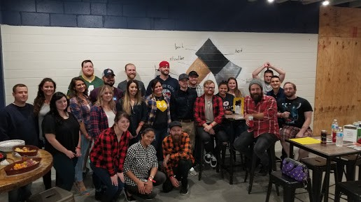 large group of people at axe throwing graduation party