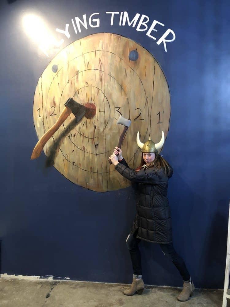 girl in viking hat by axe throwing target